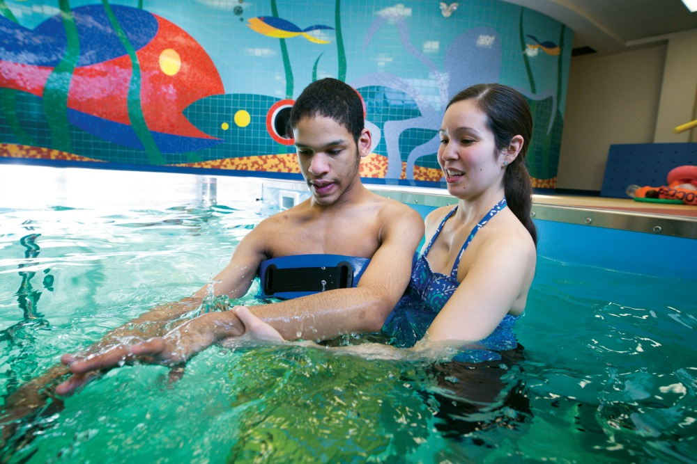 Young boy working with Physical Therapist in our Therapy Pool