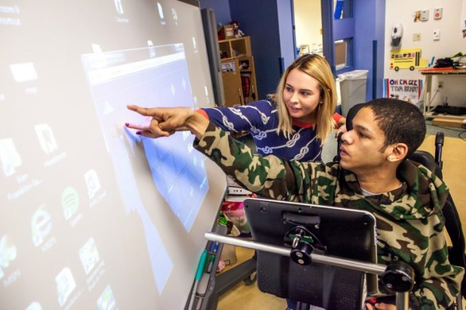 Devin working with his KDS Teacher, Kelly, using a Smart Board in the Classroom