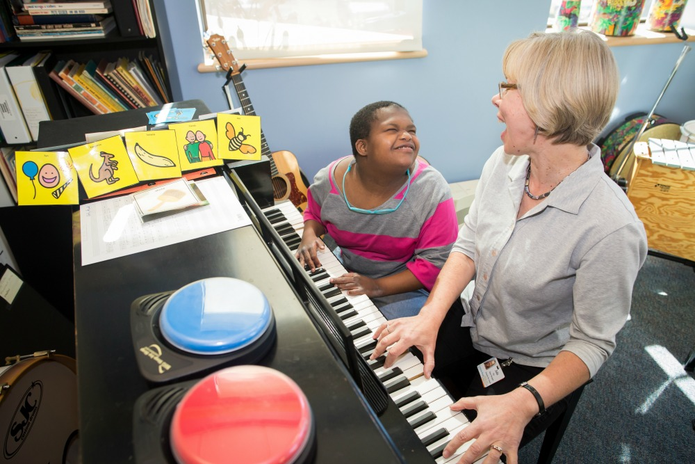 Julie, Music Therapist, working with a KDS student