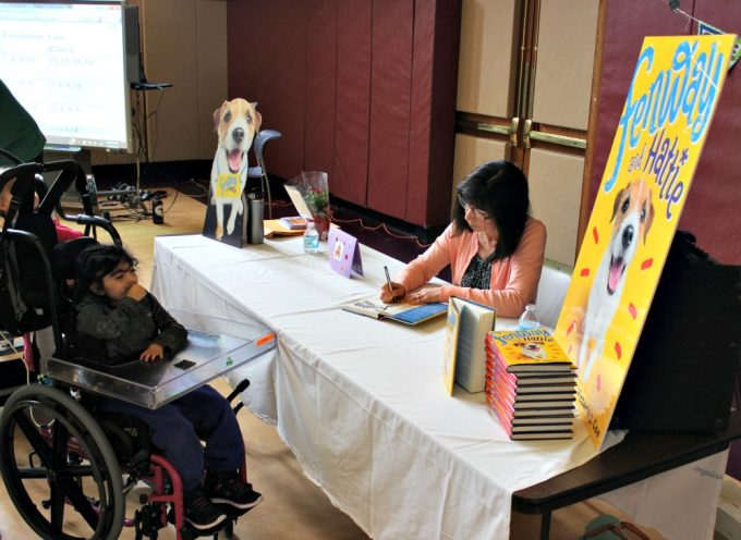 Author Victoria Coe signing copies of her book, Fenway and Hattie, for KDS students