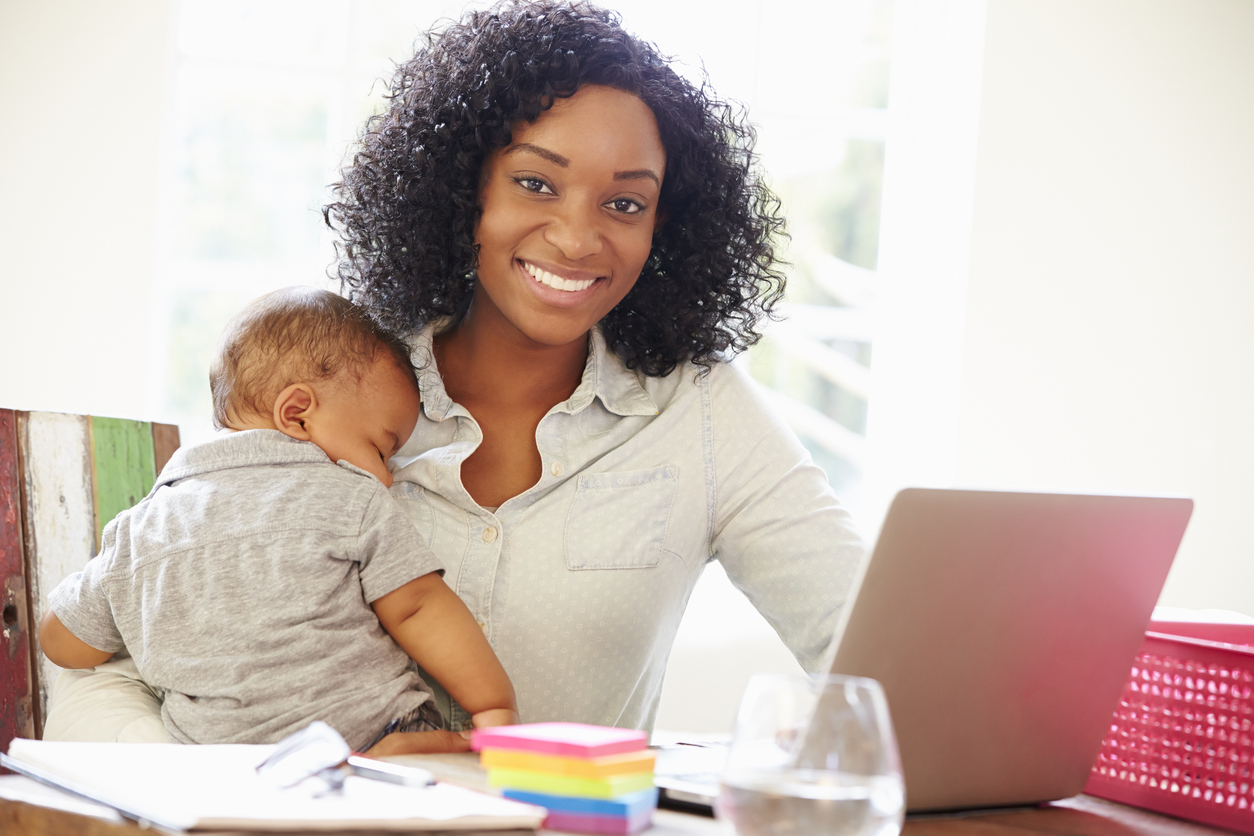 Mother With Baby Working In Office At Home With Laptop Smiling To Camera