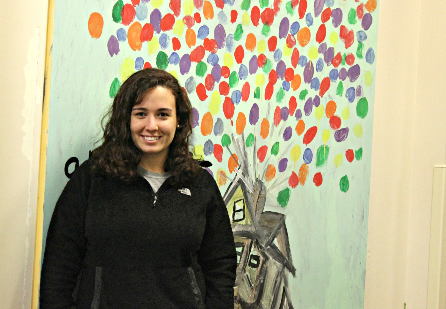 Mental Health Specialist Maria standing in front of artwork done by inpatient mental health patients