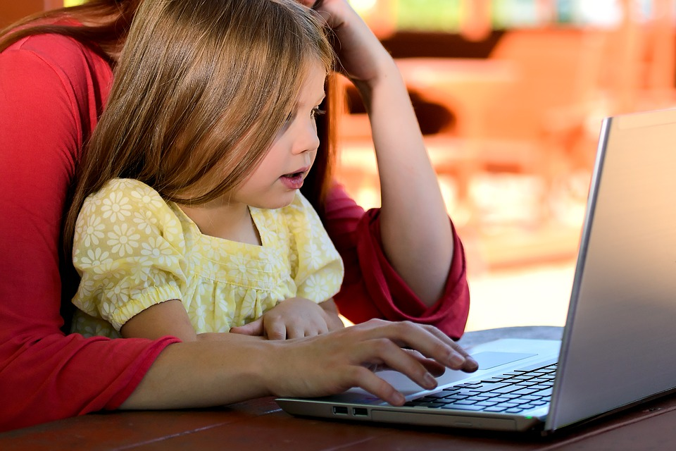 Parent and child looking at computer screen, limiting screen time